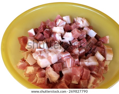 Yellow plastic bowl full of raw meat pieces close up - stock photo