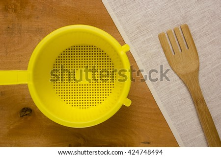 Yellow plastic colander and a napkin on a wooden table - stock photo