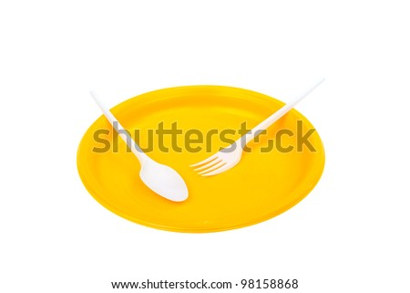 Yellow plastic plate, fork and knife on white background - stock photo