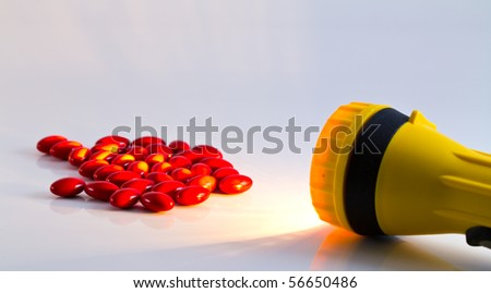 Yellow plastic pocket flash-light ang pills - stock photo