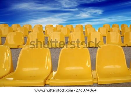 yellow plastic seats on the rostrum - stock photo