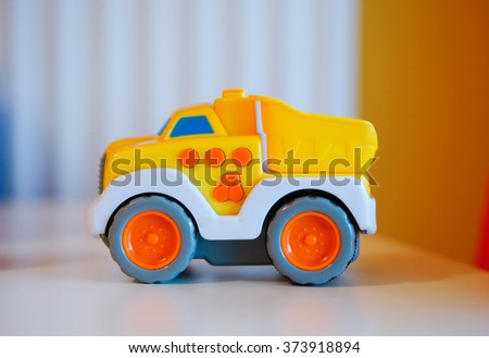 Yellow plastic toy truck with music button - stock photo