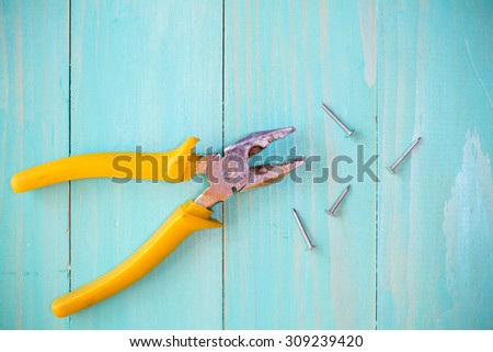 Yellow pliers and few nails on wood background - stock photo
