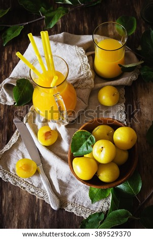 Yellow plum juice in a glass jug and ripe yellow plum on a vintage wooden table. View from above. Bio healthy food and drink. Organic diet - stock photo