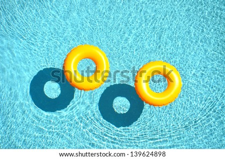 Yellow pool float, pool ring in cool blue refreshing blue pool, - stock photo