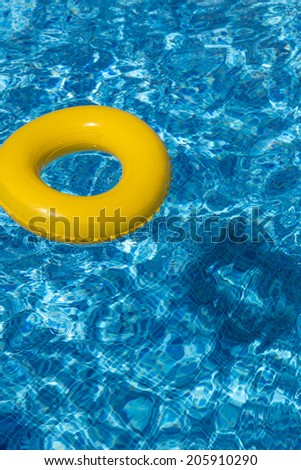 Yellow pool float, pool ring in cool blue refreshing swimming pool