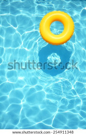 Yellow pool float, ring floating in a refreshing blue swimming pool - stock photo