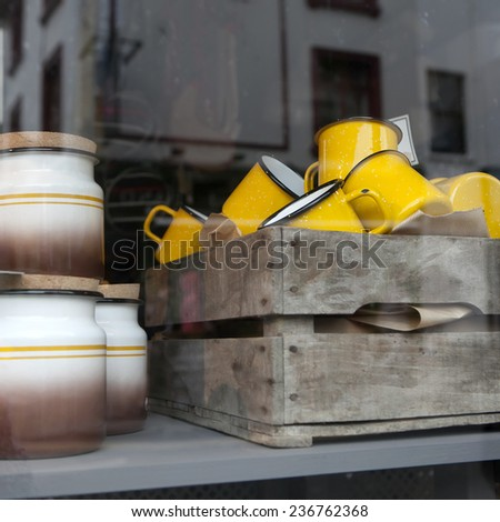 yellow porcelain cups of 1950-th years in the wooden box in the window of shop. The simple form, glazed texture, small flower image.Good for background. London flea-market - stock photo