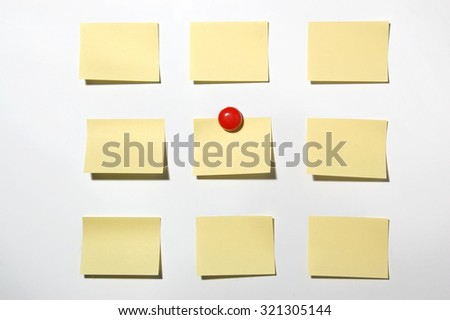 Yellow post it note and magnet button on whiteboard