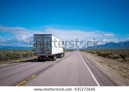 Yellow powerful big rig semi truck with refrigerated trailer running on the oncoming traffic line, overtaking vehicles in the other lane, clearly visible on the stretch of road on a plateau of Nevada