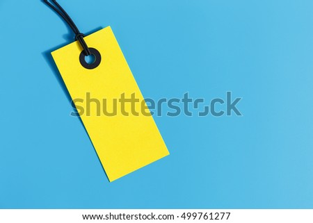 Yellow price tag on blue background with space