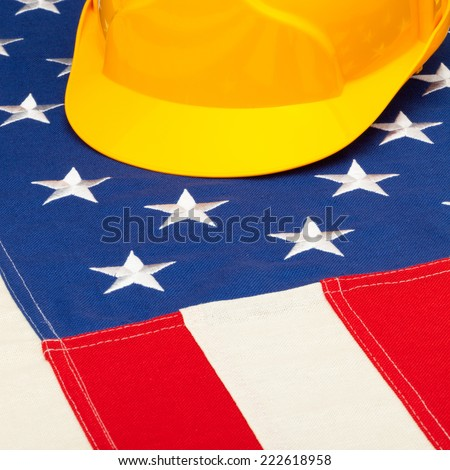 Yellow protective helmet over US flag - closeup shoot - 1 to 1 ratio - stock photo