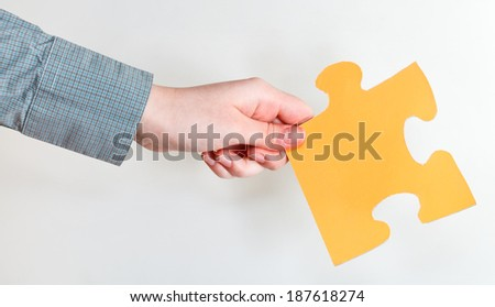 yellow puzzle piece in female hand on grey background