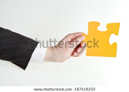 yellow puzzle piece in male hand on grey background