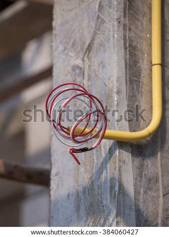 yellow PVC pipes for electrical boxes and wires buried on concrete wall at construction site