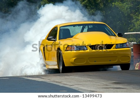 "Yellow race car ""takes off"" down the track during the race - stock photo"