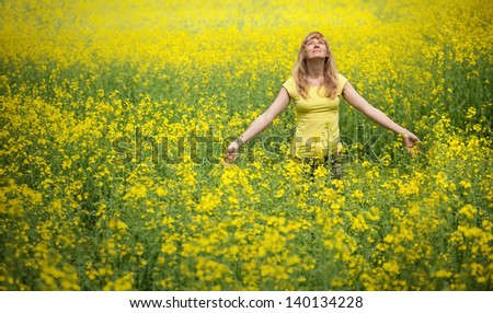 Yellow rapeseed field with woman. - stock photo