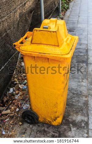 Yellow Recycle Bin in the footpath - stock photo