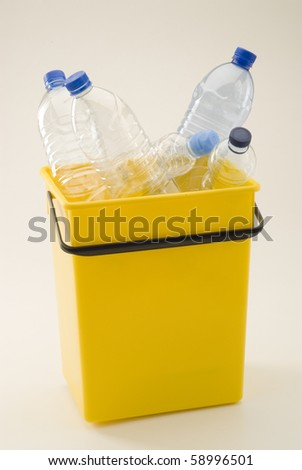 Yellow recycling bin full of plastic bottles . White background.