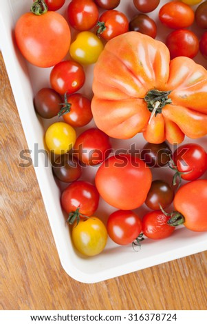 Yellow, red and black tomatoes on baking sheet - stock photo