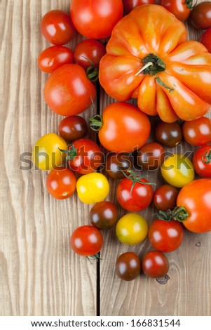 Yellow, red and black tomatoes on wooden background - stock photo
