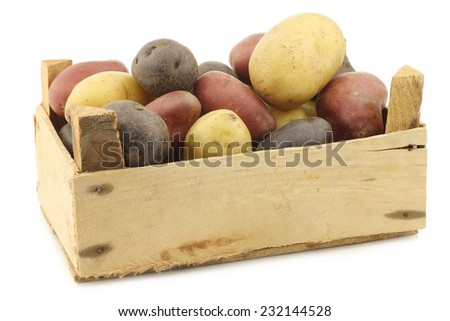 yellow, red and purple potatoes in a wooden crate on a white background