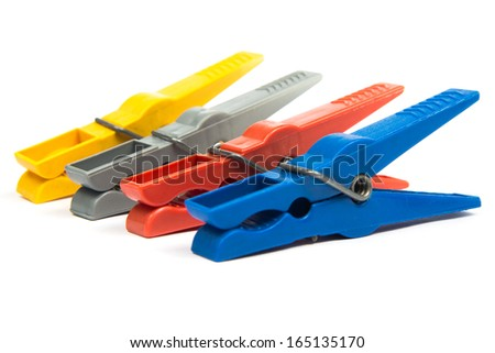 Yellow, red, gray and blue clothes pegs standing in a row next to each other