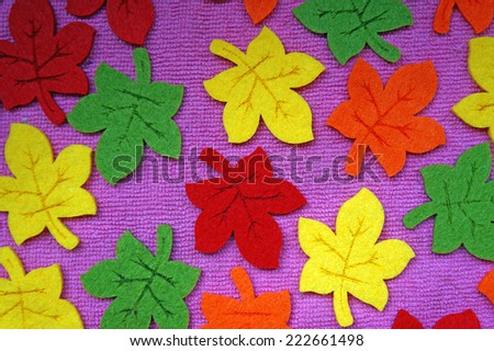 Yellow, red, orange and green Maple leaves out of felt on fabric as a background                                - stock photo