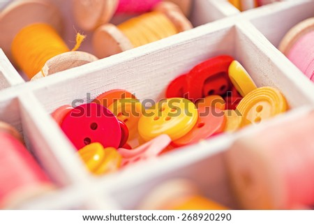 yellow, red, pink  buttons  arranged in a white wooden box - stock photo
