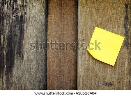 yellow reminder sticky note on wooden wall.(blank post it note) flat lat.  - stock photo