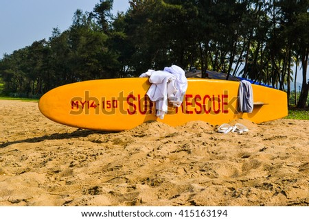 yellow rescue board on sandy beach india goa - stock photo