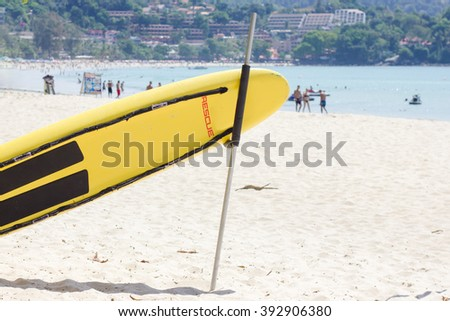 yellow rescue surfboard at beach with people in blue sea - stock photo