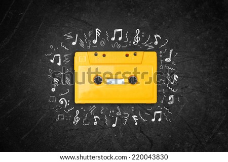yellow retro Cassette tape over blackboard. top view. music sketches - stock photo