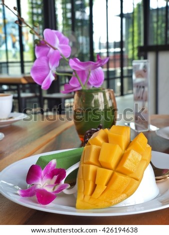 yellow ripe mango with matcha green tea mousse cake on the white dish in restaurant. - stock photo