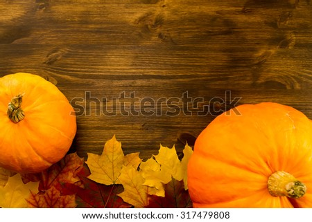 Yellow ripe pumpkin, maple leaves on wooden background. Thanksgiving, autumn. - stock photo