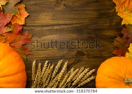Yellow ripe pumpkin, maple leaves, red apples, wheat on wooden background. Thanksgiving, autumn, homemade. - stock photo