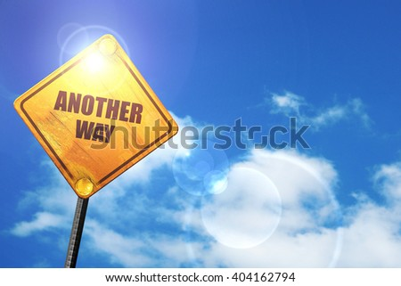 Yellow road sign with a blue sky and white clouds: another way - stock photo