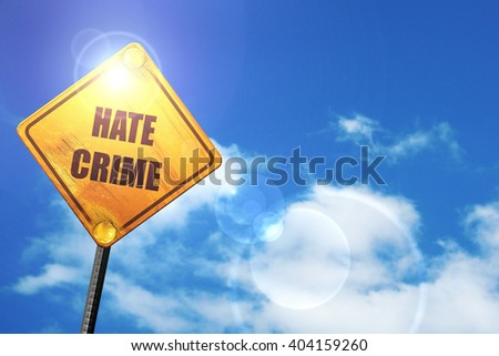 Yellow road sign with a blue sky and white clouds: Hate crime ba - stock photo