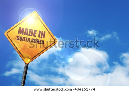 Yellow road sign with a blue sky and white clouds: Made in south korea