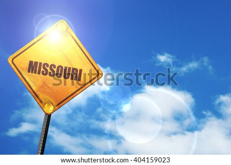 Yellow road sign with a blue sky and white clouds:  missouri
