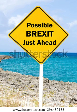 Yellow road sign with a Possible Brexit Just Ahead concept against a coastal setting with a partly cloudy sky background. - stock photo