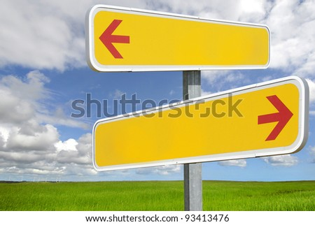 yellow roadsign with arrows on beautifull cloudy blue sky with green landscape - stock photo