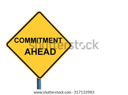 Yellow roadsign with COMMITMENT AHEAD message isolated on white background