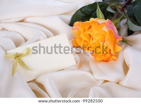 Yellow rose and a card on a gentle silk