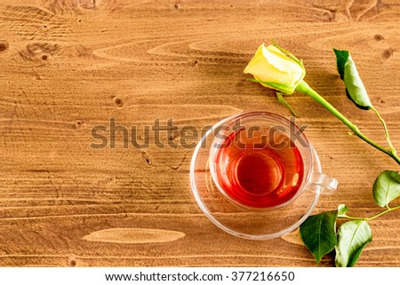 Yellow rose and a cup of black tea in a transparent glass cup on rustic wooden table top. Top view. Flat.
