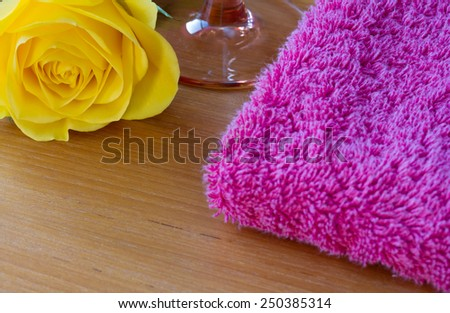 Yellow rose with a wine glass and a pink towel - stock photo