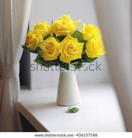 Yellow roses bouquet on a windowsill - stock photo