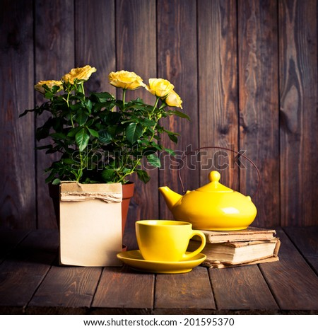 yellow roses in pot, teapot, tea cup and old books on wooden table