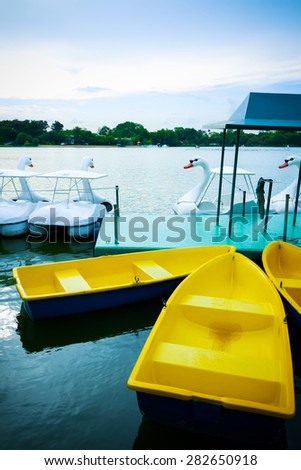 yellow row boats floating in lagoon, in the park, early in the evening - stock photo