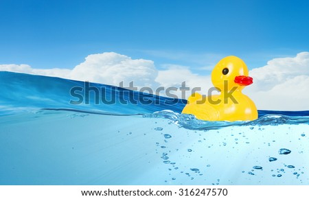 Yellow rubber duck toy floating in water - stock photo